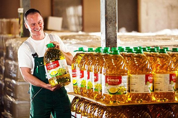 Daniel Dreyer, Mitarbeiter der Firma Sachsenfett, stappelt im Firmenlager Flaschen mit Öl