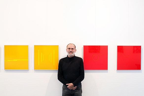 Galerist Eberhard Klinger zwischen Bilder der Ausstellung Konkrete Spektrale